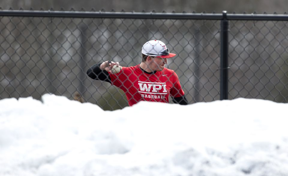 With mounds of the white stuff piled in the foreground, a WPI player makes a throw recently on one of the three snow-cleared turf fields at the New England Baseball Complex.