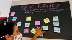 At Ula Cafe in Jamaica Plain, co-owner Beth Santos looks at some of the sticky notes on the pay-it-forward wall, where customers can buy items to be redeemed later by anybody in need.