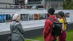 Viewers admire the Boston Camera Club's photo banner exhibit at Fan Pier in the Seaport District.