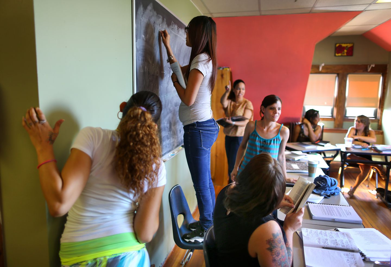 Microcollege students write on chalkboard in class.