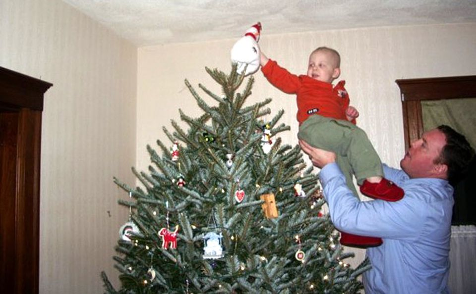 """When Will was 2, his father Pat gave him the job of """"tree topper"""" at Christmas. Each year, Pat hoists Will up to the top of the tree as his mother, Dina, takes the photo. It has become their most important family tradition."""