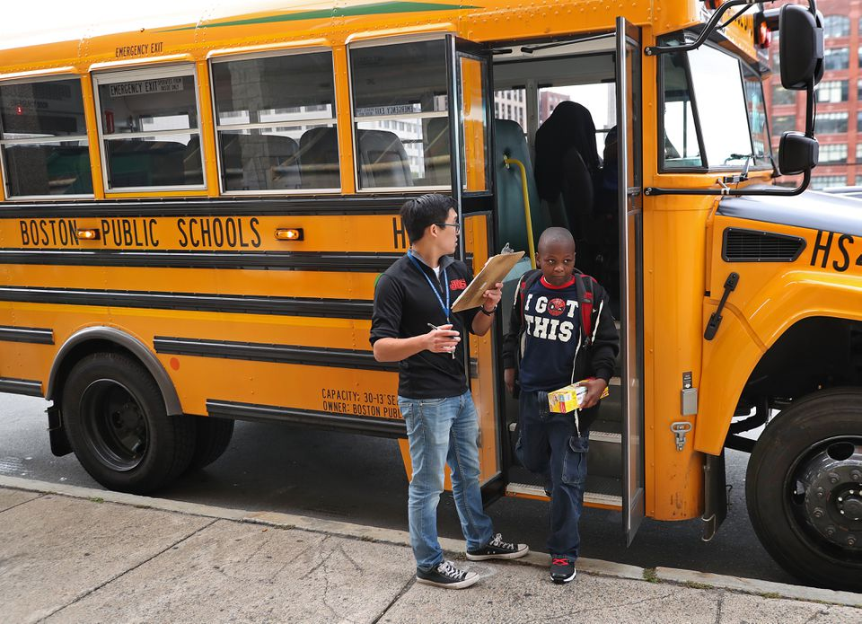 A Boston Public School employee monitored the arrival of a bus at the Josiah Quincy School on the first day of school. David L Ryan/Globe Staff
