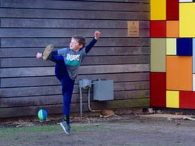 A young boy kicked a football at Discovery Green in downtown Houston.