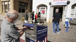 A voter submits a ballot in an official drop box during early voting in Athens, Ga., Oct. 19, 2020. A new Georgia law, among other constraints on voting, restricts the availability of drop boxes for absentee ballots.