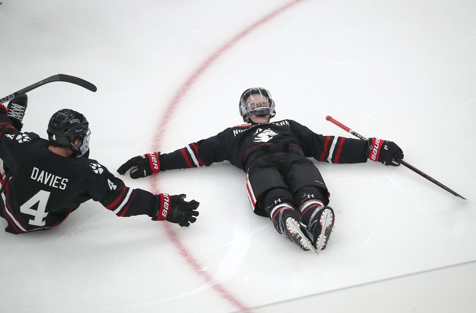 Northeastern's Tyler Madden (right) makes an ice angel alongside Jeremy Davies after scoring in overtime atTD Garden.
