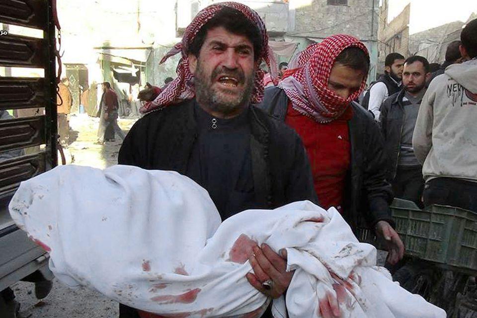 In an image shot by a citizen, a man carried the body of a child reportedly killed in a Syrian airstrike in Aleppo.