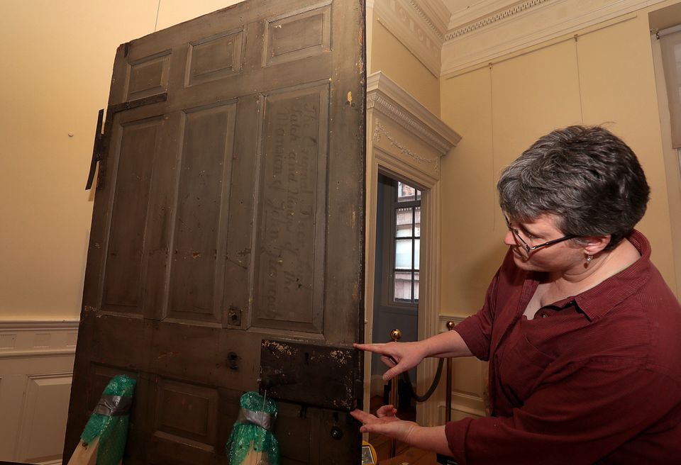 North Bennet street school preservation carpenter Angela Larimer points out the original lock on the original Hancock door, which will be mounted and on exhibit at Boston's Old Statehouse.