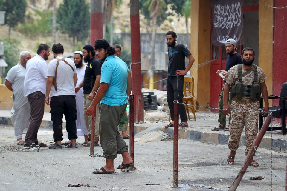 Members of the Nusra Front and civilians stood near a Syrian courthouse where a suicide bomb attack took place in August.