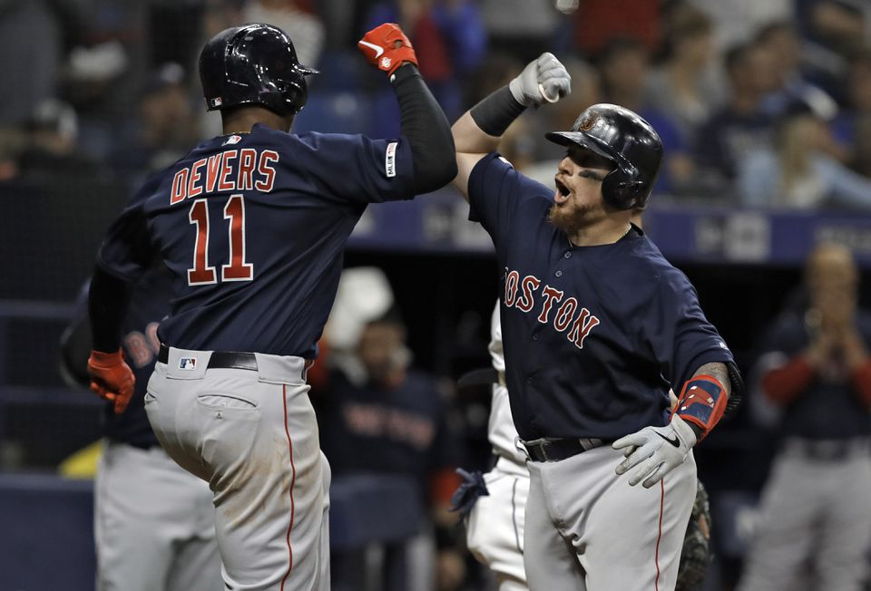 Christian Vazquez is greeted at the plate by Rafael Devers, who scored ahead of him on his two-run homer in the fifth inning.