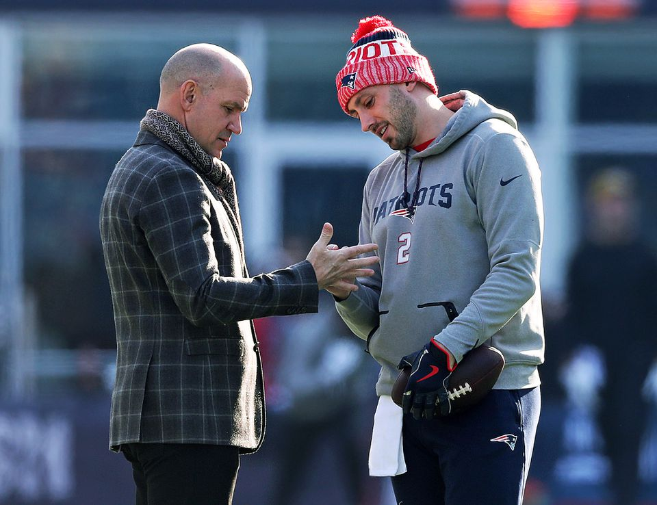 About two hours before kickoff, Patriots backup quarterback Brian Hoyer (right) was out throwing some passes, when he stopped and was pointing out a spot on an unidentified man's right hand.