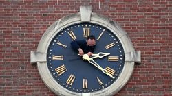 Philip D'Avanza installed the newly repaired gold-leafed clock hands on the cupola at Newton City Hall late last month.