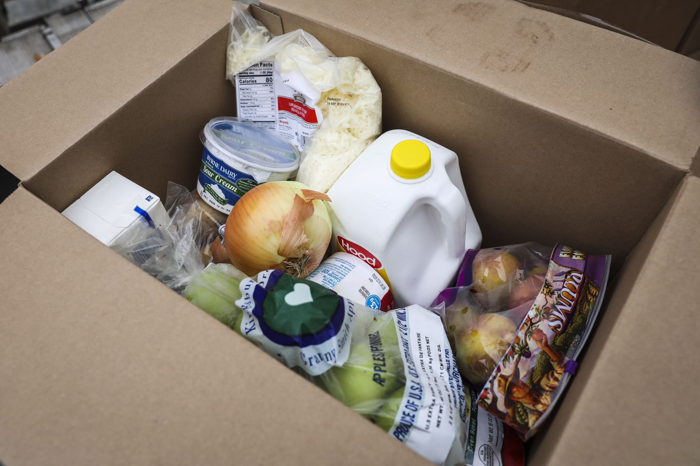 A box filled with produce, milk, and other essentials waits to be distributed at a Chelsea Pop-up Food Pantry, organized by the city of Chelsea.