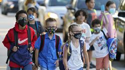 Students, some wearing protective masks, arrive for the first day of school at Sessums Elementary School in Riverview, Fla. The on-again, off-again ban imposed by Republican Gov. Ron DeSantis to prevent mandating masks for Florida school students is back in force. The 1st District Court of Appeal ruled Friday, Sept. 10, that a Tallahassee judge should not have lifted an automatic stay two days ago that halted enforcement of the mask mandate ban.
