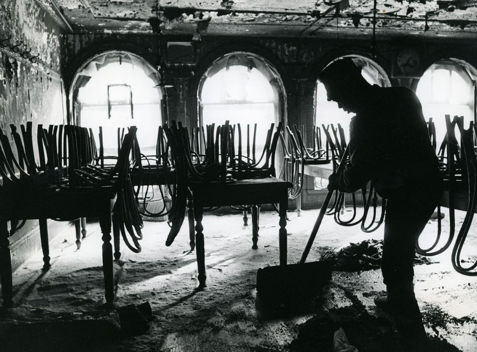 A person cleaned the inside of the burned dining room of Durgin-Park after a fire Feb. 7, 1968.
