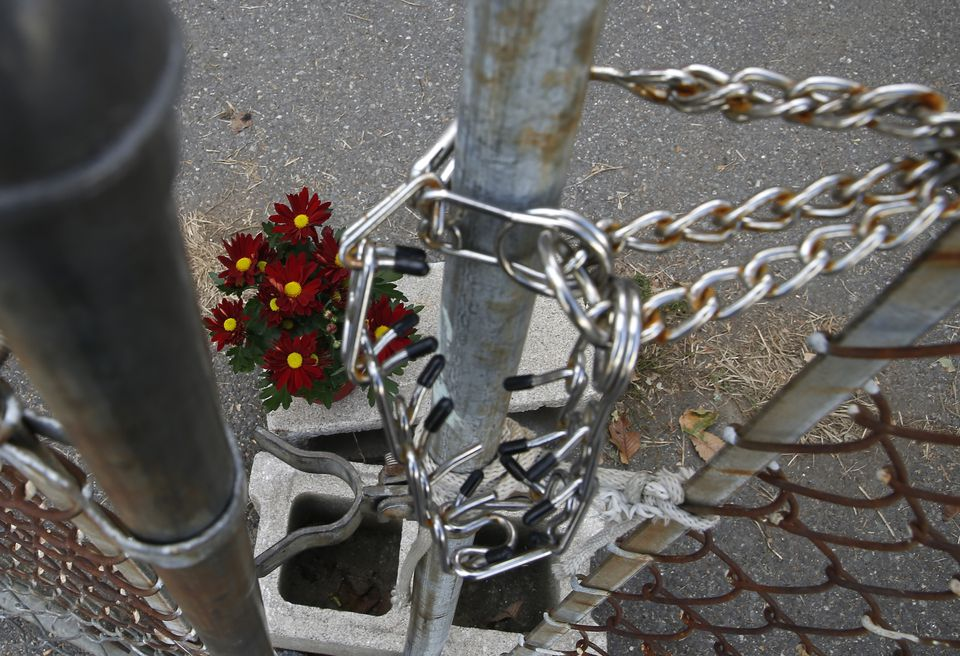 Flowers sat inside the fenced in area where a seven-year-old boy was killed by two pit bulls is seen in Lowell.