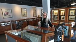 Board chair Ellyn Moller cleaned some vitrines at Milton Art Museum's new location in Brockton.