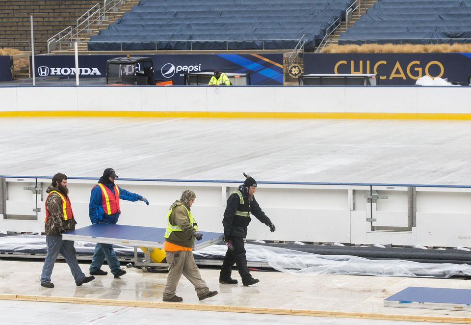 Crews work to set up a hockey rink and staging for the NHL Winter Classic game between the Chicago Blackhawks and the Boston Bruins at Notre Dame Stadium in South Bend, Ind.