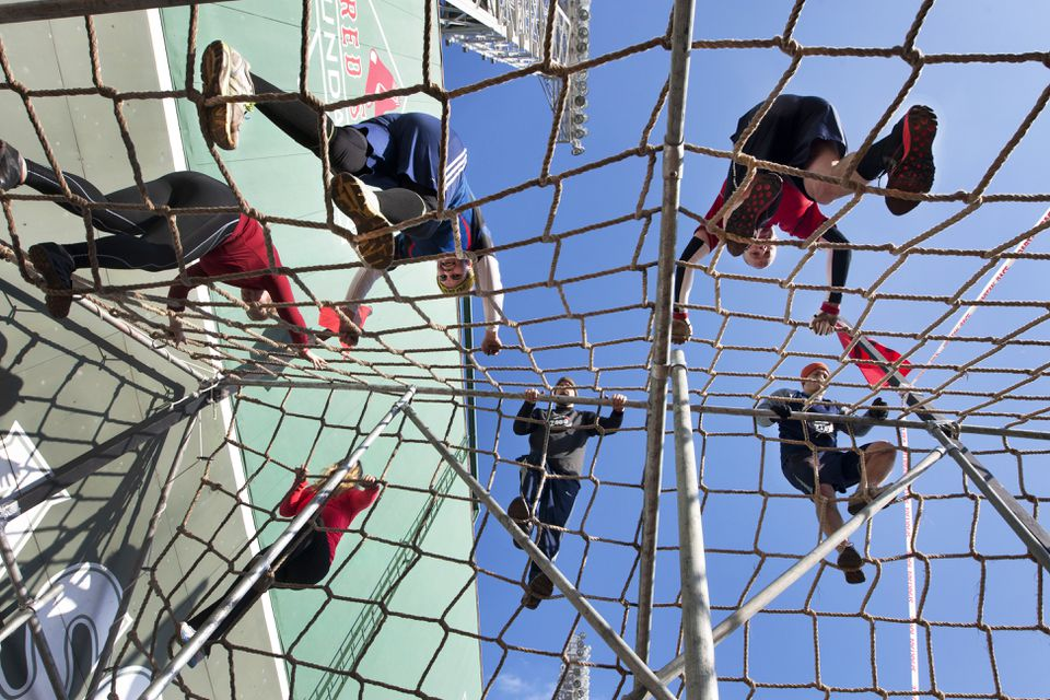 Spartan Race participants scale cargo netting in front of the Green Monster at Fenway Park.