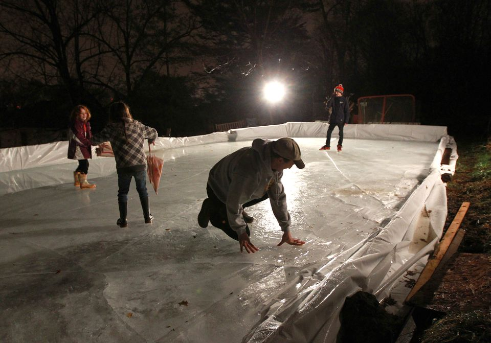 In January of 2012, Jon Frankel of Brookline (kneeling third from the left) checked out the condition of his backyard rink as daughters Mia and Wendy and son Adam slip and slide on the thin ice.