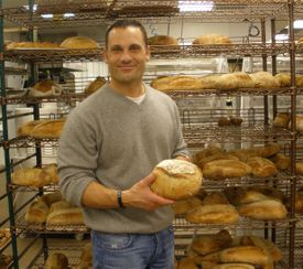 16tuscan - Joe Faro, owner of Tuscan Market and Tuscan Kitchen restaurant in Salem, NH, with some of the day's breads. (Lisa Zwirn)