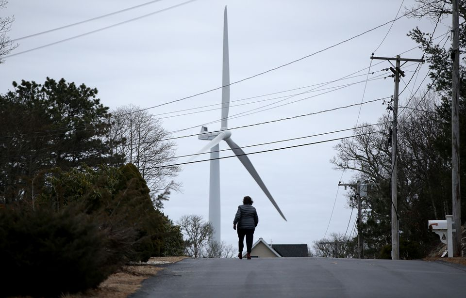 A woman walked along Westmoreland Drive in Falmouth, in the shadow of one of the city's wind turbines.