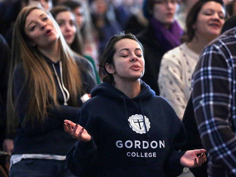 Junior Paula Gomes (center) and other Gordon College students took part in a required chapel service last month.