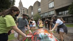 Prospective students and their parents touched the Greek Rock while taking a tour of Boston University on Tuesday.