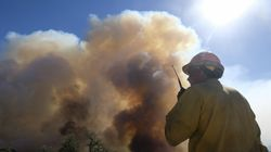 A firefighter watches as smoke rises from a wildfire in Goleta, Calif., on Oct. 13. Sweeping assessments released Thursday by the White House, the US intelligence community, and the Pentagon conclude that climate change will exacerbate longstanding threats to global security.
