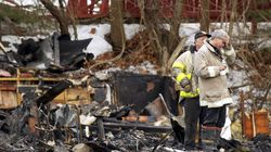 A firefighter holds his hand to his forehead as he stands amidst the rubble at the scene of a deadly fire at The Station nightclub in West Warwick, R.I. Friday, Feb. 21, 2003.