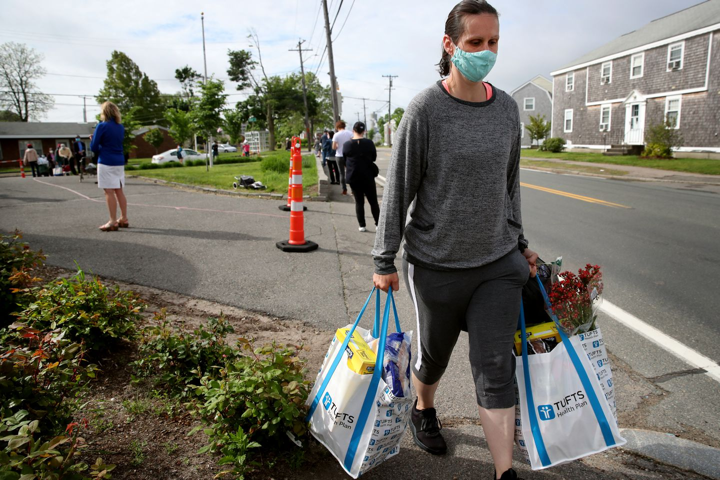A Quincy resident receives food from the South Shore YMCA Germantown Neighborhood Center Food Pantry in Quincy in May.