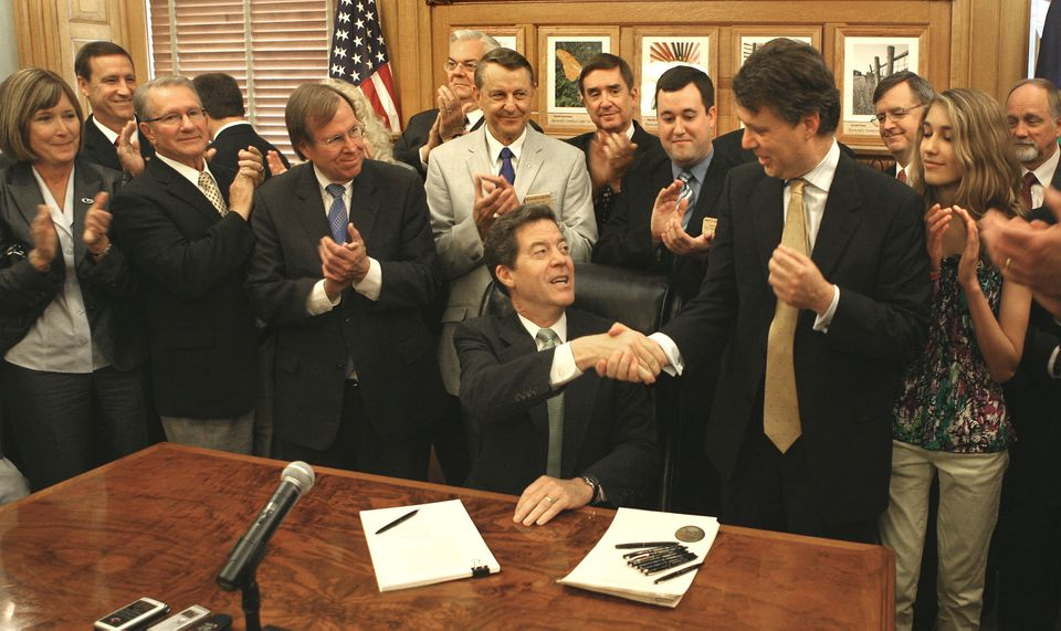 """Governor Sam Brownback of Kansas (seated) in 2012 signed into law one of the largest tax cut bills in Kansas history, saying it would create """"tens of thousands of new jobs."""""""