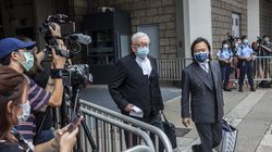 Lawyer Lawrence Lau (right) and senior counsel Clive Grossman (center) left the holding area of the High Court in Hong Kong on Friday after visiting their client Tong Ying-kit, who was sentenced to nine years in prison for terrorism and inciting secession in the first trial conducted under a national security law imposed by China.