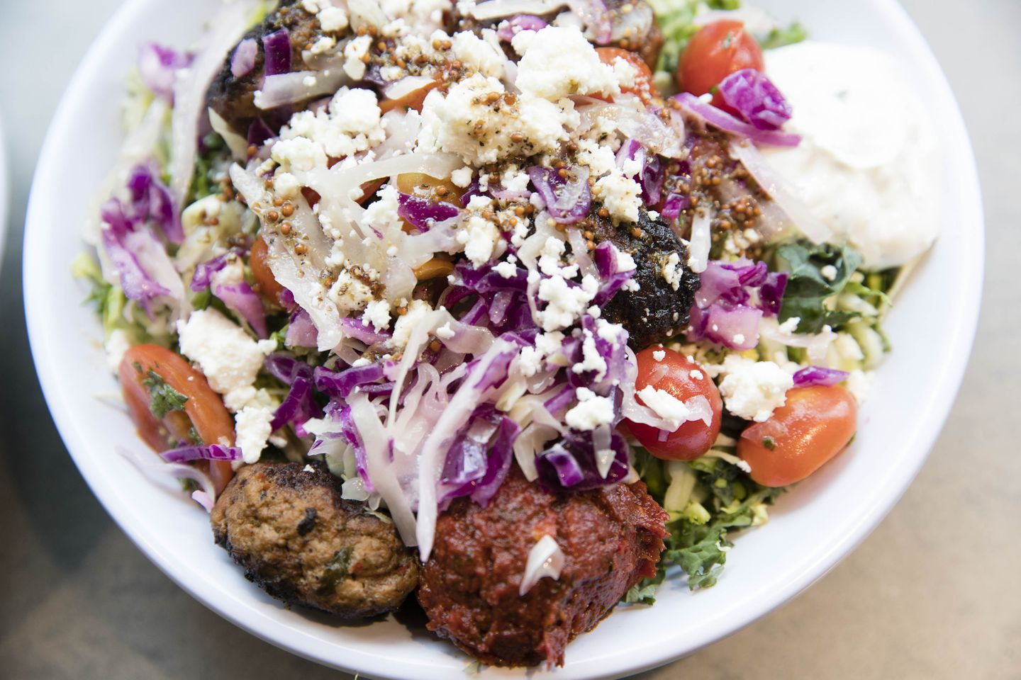A super greens bowl with spicy lamb meatballs, hummus, tzatziki, harissa, tomato, onion, cabbage slaw, crumbled feta, and greek vinaigrette at Cava on Boylston Street.