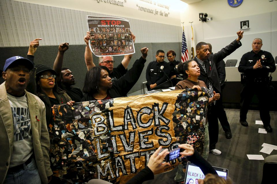 """Demonstrators carried a """"Black Lives Matter"""" banner while protesting the death of Ezell Ford during a meeting of the Los Angeles Police Commission in June."""