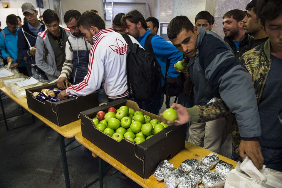 Refugees selected food and drink offered by volunteers at the Schoenefeld regional railway station near Berlin.