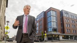 Colby College's president, David Greene, on Main Street in Waterville, in front of the Bill and Joan Alfond Main Street Commons, one of the college's revitalization projects in the Maine city's downtown.