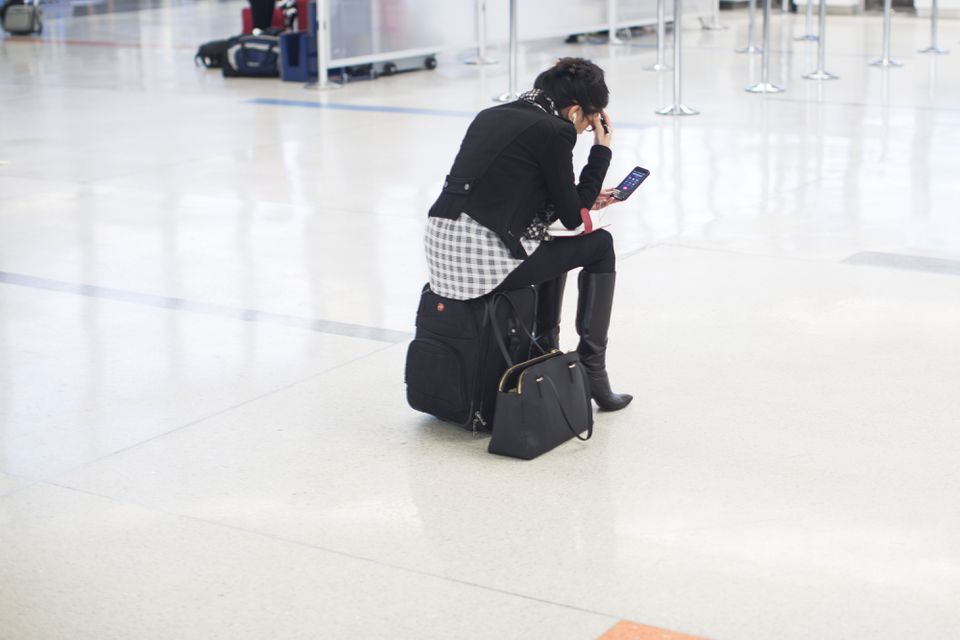 A woman waited at Logan International Airport on Wednesday.