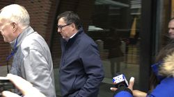 Former Massachusetts State Representative David Nangle, center, leaves the federal courthouse after his initial appearance in February of 2020.