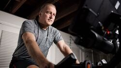 Anthony Flint rides an exercise bike as part of his physical therapy during his recovery from Guillain-Barré Syndrome.