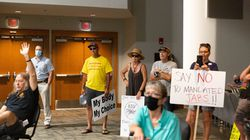 Demonstrators hold signs during a community town hall to promote Covid-19 vaccinations with Arkansas Governor Asa Hutchinson at Arkansas State University Mountain Home (ASUMH) in Mountain Home, Arkansas, on July 16.