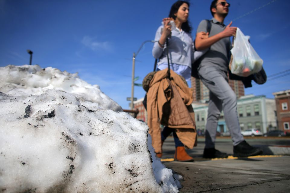 The last of a snow pile melted away as pedestrians in short sleeves walked along Commonwealth Avenue in Brighton on Tuesday.