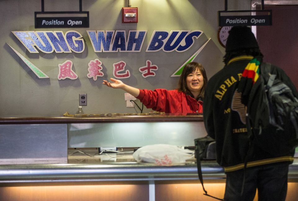 A worker at the Fung Wah Bus ticket booth at South Station sold passengers tickets for a bus headed to New York.