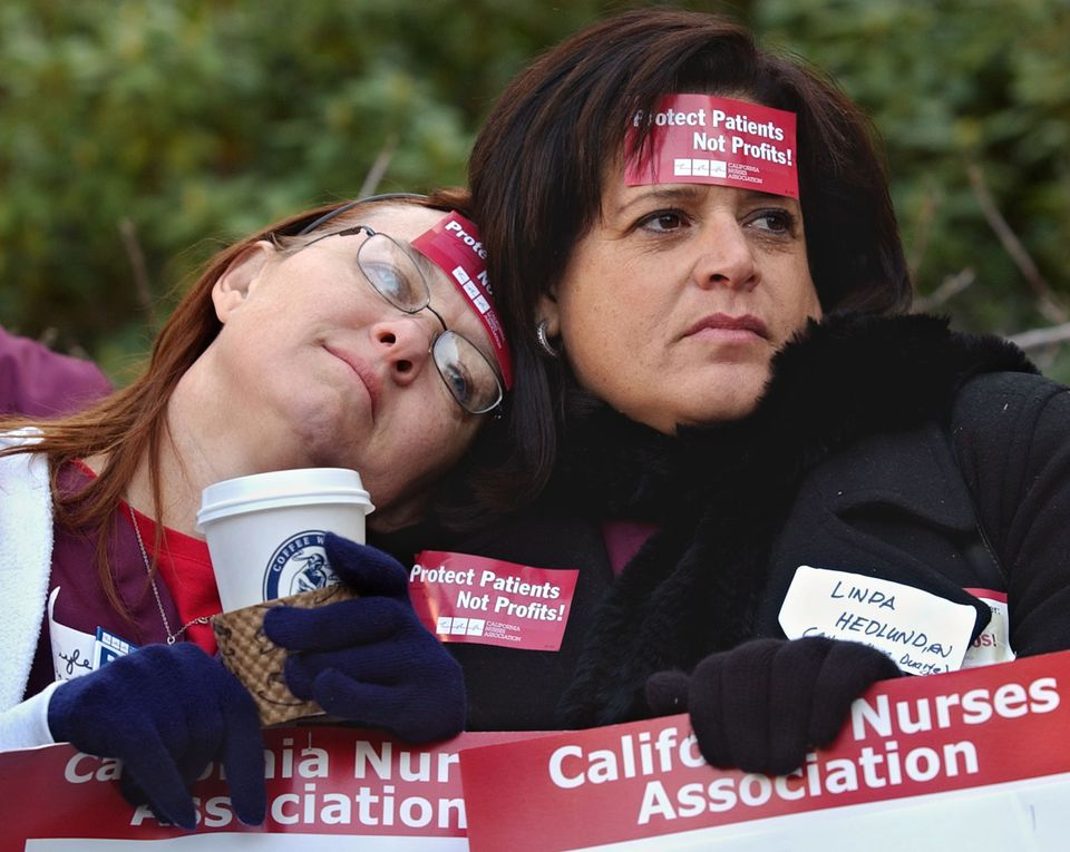 Gaylee Cox (left) and Linda Hedlund, who both worked as pediatric nurses at the City of Hope Hospital in Los Angeles, huddled together to stay warm during a nurses rally in 2004.