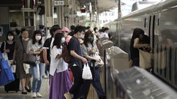Passengers wearing face masks to help curb the spread of the coronavirus get on board a west-bound bullet train at Tokyo Station in Tokyo.