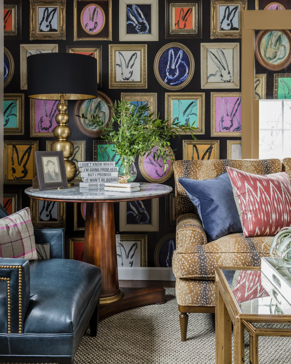 In the living room, the Hunt Slonem for Lee Jofa wallpaper takes center stage. The antelope-pattern chenille Wesley Hall sofa holds bold-hued throw pillows. A Wesley Hall blue leather armchair adds a textural dimension. The marble-top table is by Lillian August for Hickory White.