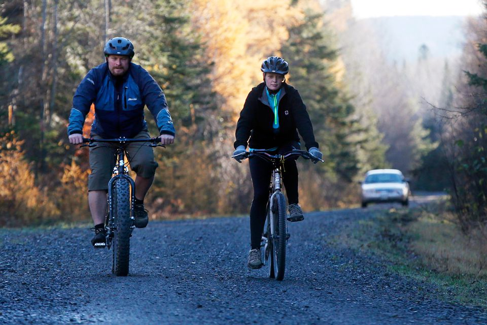 Nurse Kaci Hickox (right) and her boyfriend, Ted Wilbur, were followed by a Maine State Trooper as they rode bikes on a trail near her home in Fort Kent on Thursday.