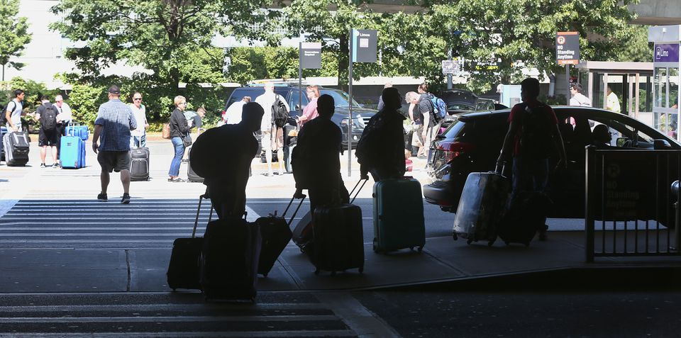 Passengers waited outside of Terminal A at Logan Airport.