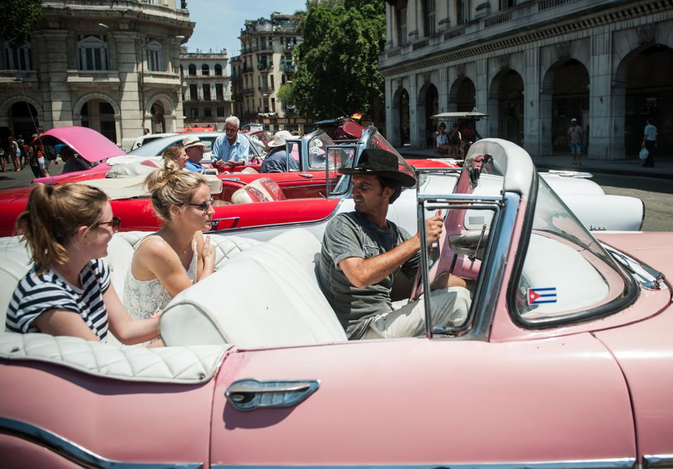 Tourists from the United States sit in an old American car in Havana.