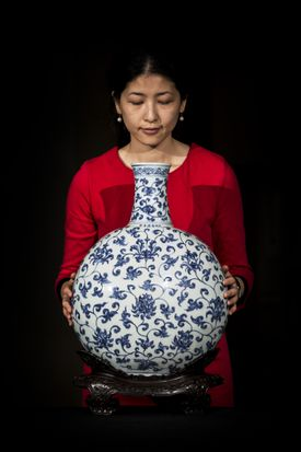 A British Museum employee posed behind a 15th century Imperial Ming Vase.