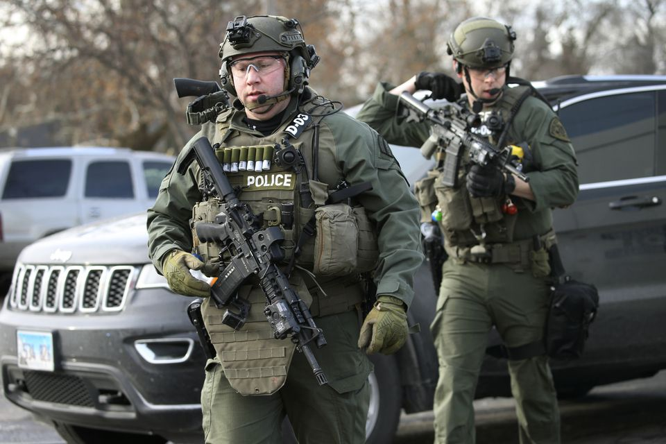 Heavily armed police officers gathered at the crime scene.